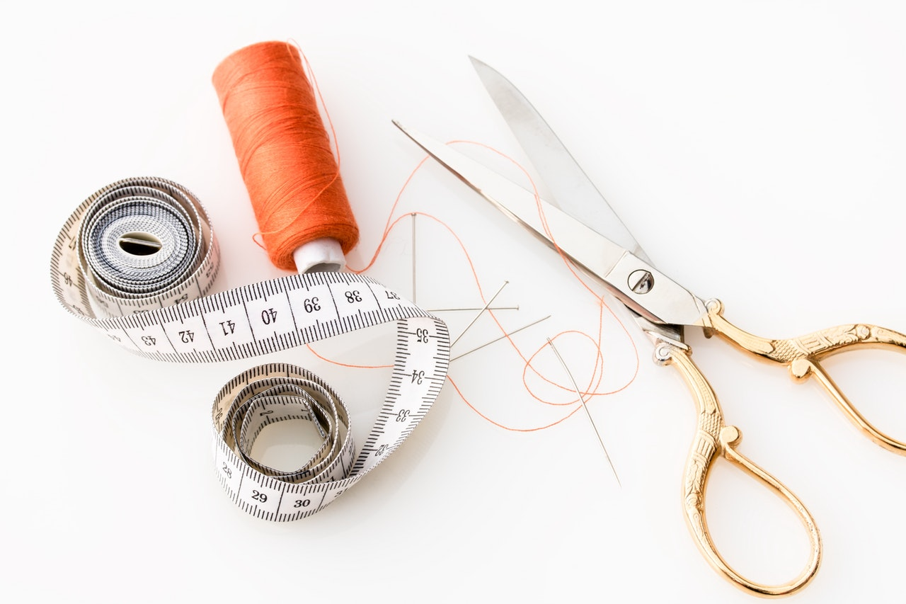 measuring tape, orange thread roll, pins, needle and scissors