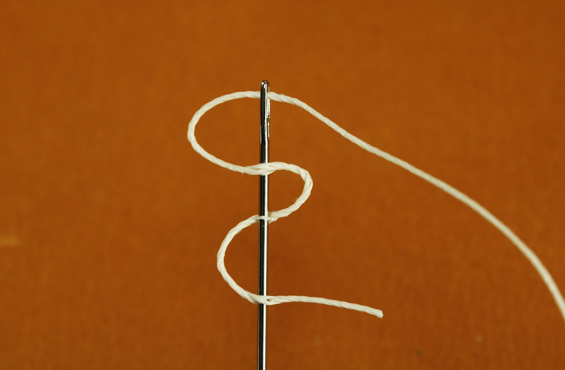 Inside the hole of the best hand sewing needle is a white thread
