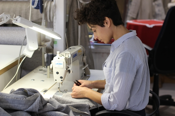 woman  working on  using sewing machine